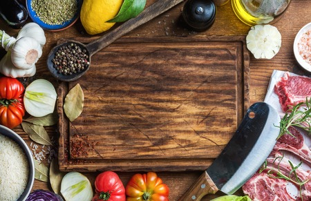 Ingredients for cooking healthy meat dinner. Raw uncooked lamb chops with vegetables, rice, herbs and spices over rustic wooden background, dark chopping board in center with copy space. Top view