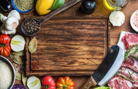 Bestandteile für das Kochen gesundes Fleisch Abendessen. Raw ungekocht Lammkoteletts mit Gemüse, Reis, Kräutern und Gewürzen über rustikale Holz Hintergrund, dunkel Schneidebrett in der Mitte mit Kopie Raum. Aufsicht Standard-Bild
