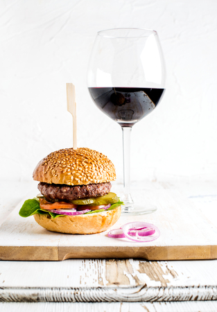 Fresh homemade burger on wooden serving board with onion rings and glass of red wine. White background, selective focus