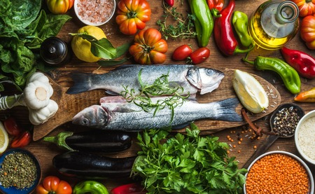 Raw uncooked seabass fish with vegetables, grains, herbs and spices on chopping board over rustic wooden background, top view
