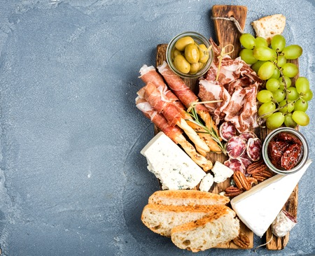 Cheese and meat appetizer selection. Prosciutto di Parma, salami, bread sticks, baguette slices, olives, sun-dried tomatoes, grapes and nuts on rustic wooden board over grey concrete textured backdrop, top view, copy space