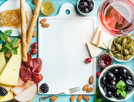 white wine: Summer wine snack set. Glass of rose, meat, cheese, olives, honey, bread sticks, nuts, capers and berries with white ceramic board in center, blue wooden background, top view, copy space