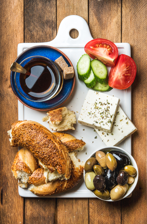 Turkish traditional breakfast with feta cheese, vegetables, olives, simit bagel and tea on white ceramic board over brown wooden background. Top view