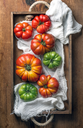 Colorful Heirloom tomatoes in rustic wooden tray, top view