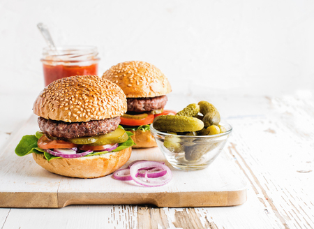 Two fresh homemade burgers, pickles, ketchup and onion rings on white wooden serving board. White background, selective focus, horizontal composition Banco de Imagens