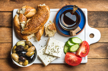 Turkish traditional breakfast with feta cheese, vegetables, olives, simit bagel and black tea on white ceramic board over wooden background. Top view, horizontal composition Stok Fotoğraf - 59877700