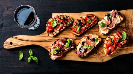 Brushetta fixé pour le vin. Variété de petits sandwichs avec prosciutto, tomates, fromage parmesan, basilic frais et de crème balsamique servi avec un verre de vin rouge à bord en bois rustique sur fond sombre, vue de dessus