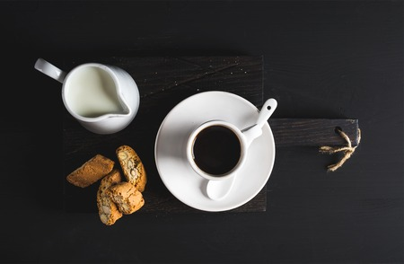 creamer: Cup of hot espresso, creamer with milk and cookies on dark rustic wooden board over black background, top view, horizontal composition