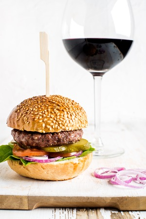 Fresh homemade burger on white wooden serving board with onion rings and glass of red wine. White background, selective focus, vertical composition