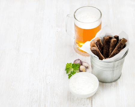 pilsener: Beer snack set. Pint of pilsener in glass mug and rye bread croutons with garlic cream cheese sauce over white painted old wooden background, top view, copy space, selective focus Stock Photo
