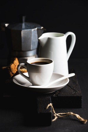 creamer: Italian coffee set for breakfast. Cup of hot espresso, creamer with milk, cantucci and moka pot on dark rustic wooden board over black background, selective focus, vertical composition