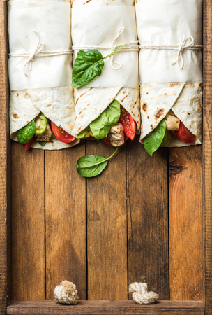 lunch tray: Healthy lunch snack. Three tortilla wraps with grilled chicken fillet and fresh vegetables on rustic wooden tray. Top view, copy space, vertical composition Stock Photo
