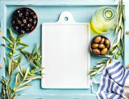 ceramic bottle: Two bowls with pickled green and black olives, olive tree sprigs and bottle of olive oil with white ceramic board in center. Blue Turquoise background, copy space, top view Stock Photo