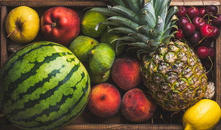 friut: Summer friut variety on wooden background, top view. Watermelon, pineapple, lemon, figs, peach, sweet cherry and apple