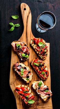 Brushetta fixé pour le vin. Variété de petits sandwichs avec prosciutto, tomates, fromage parmesan, basilic frais et de crème balsamique servi avec un verre de vin rouge à bord en bois rustique sur fond sombre, vue de dessus Banque d'images