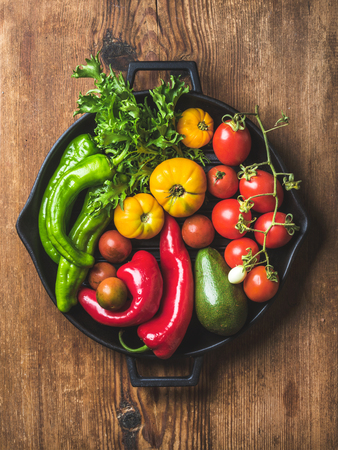 Fresh raw vegetable ingredients for healthy cooking or salad making in black grilling iron pan over rustic wooden background, top view, vertical composition. Diet or vegetarian food concept Stock Photo