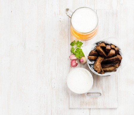 pilsener: Beer snack set. Pint of pilsener in mug and rye bread croutons with garlic cream cheese sauce over white painted old wooden background, top view, copy space Stock Photo