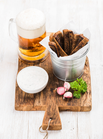 pilsener: Beer snack set. Pint of pilsener in mug, open glass beer bottle, rye bread croutons with garlic cream cheese sauce served with fresh parsley and garlic on rustic wooden board over white painted old wooden background, top view, vertical composition, select