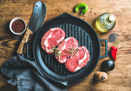 rib eye: Ingredients for cooking Rib eye roast beef steak on black iron grilling pan over wooden background, top view, horizontal composition