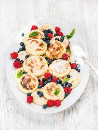 ukranian: Syrniki or cottage cheese pancakes with fresh forest berries and sour cream sauce in serving dish over white wooden background, selective focus. Russian and Ukranian cuisine