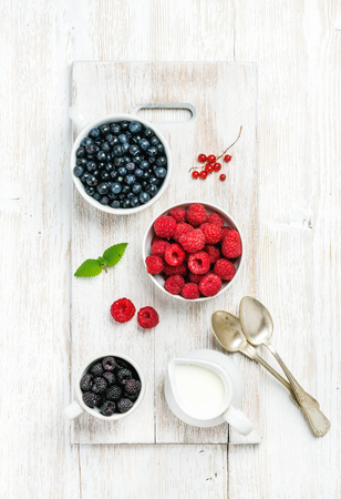 bilberries: Rasberries, blackberries and bilberries in bowls served with fresh mint, red currant and milk on white painted wooden background, top view, vertical composition