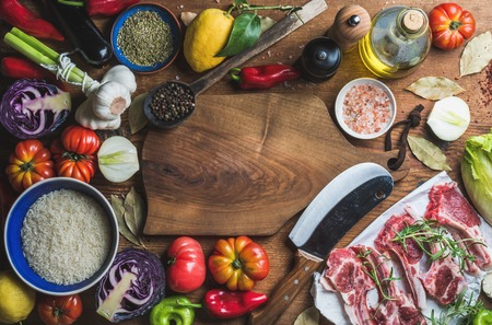 Ingredients for cooking dinner. Raw uncooked lamb meat chops, rice, oil, spices and vegetables over wooden background, top view, copy space Stock Photo