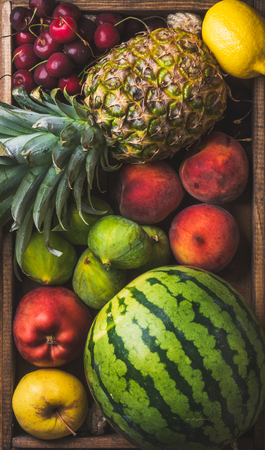 friut: Summer friut variety in wooden tray over wooden background, top view. Watermelon, pineapple, lemon, figs, peach, sweet cherry, apple
