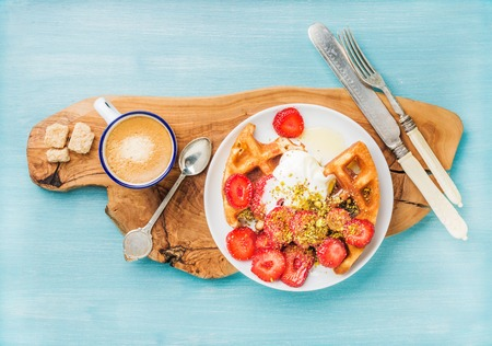 Breakfast set. Warm homemade belgium waffles with whipped cream, strawberry, maple syrup and crushed pistachios, cup of espresso and cubes of brown sugar on olive rustic wooden board over blue painted wooden background, top view, horizontal composition