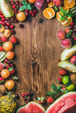 Summer fresh fruit variety over rustic wooden background, top view, copy space, horizontal composition Stock Photo