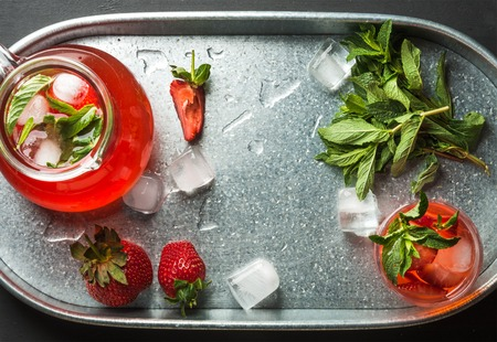 silver bars: Homemade strawberry lemonade in glass and jug with mint and ice, served with fresh berries in metal tray, top view, horizontal composition