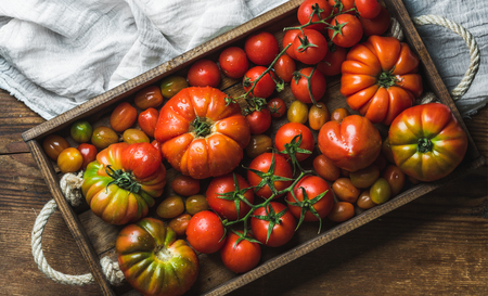Colorful tomatoes of different sizes and kinds in dark wooden tray over light textile and rustic wooden background, top view, horizontal composition Stock Photo