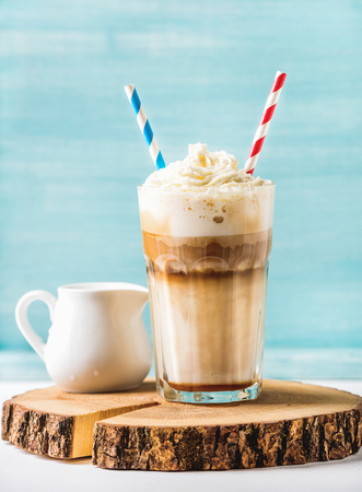 macchiato: Latte macchiato with whipped cream in tall glass with two straws and pitcher on round wooden board over blue painted wall background, selective focus, vertical composition