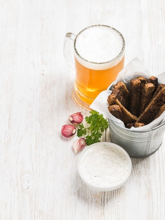 pilsener: Beer snack set. Pint of pilsener in tall mug and rye bread croutons with garlic cream cheese sauce over white painted old wooden background, top view, copy space, selective focus Stock Photo