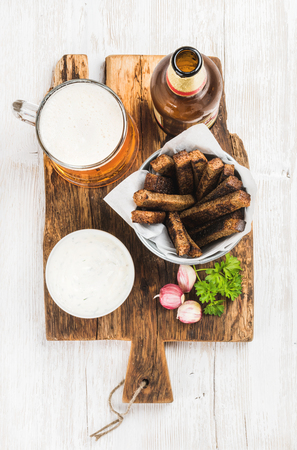 pilsener: Beer snack set. Pint of pilsener in mug, open glass beer bottle, rye bread croutons with garlic cream cheese sauce on rustic wooden board over white painted old wooden background, top view, vertical composition Stock Photo