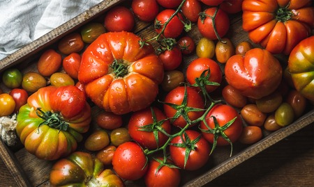 Colorful tomatoes of different sizes and kinds in dark wooden tray, top view, horizontal composition Stock Photo