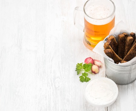 pilsener: Beer snack set. Pint of pilsener in mug and rye bread croutons with garlic cream cheese sauce over white painted old wooden background, top view, copy space, selective focus