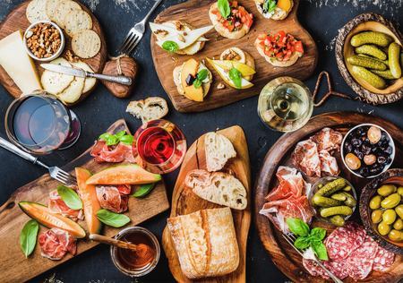 Italian antipasti wine snacks set. Brushettas, cheese variety, Mediterranean olives, pickles, Prosciutto di Parma with melon, salami and wine in glasses over black grunge background, top view 写真素材
