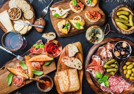 Italiaanse antipasti wijn snacks. Brushettas, kaas ras, mediterrane olijven, augurken, Prosciutto di Parma met meloen, salami en wijn in glazen over zwarte grunge achtergrond, bovenaanzicht Stockfoto