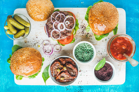 Homemade beef burgers with onion rings, pickles, fresh vegetables, spices, sun-dried tomatoes and tomato sauce on serving wooden board over blue painted background. Top view, horizontal composition Stock Photo