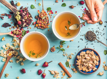 Two cups of healthy herbal tea with mint, cinnamon, dried rose and camomile flowers in spoons and man's hand holding spoon of honey, blue background, top view