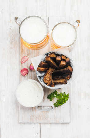 pilsener: Beer snack set. Two mugs of pilsener, rye bread croutons with garlic cream cheese sauce served with fresh herb and garlic over white painted old wooden background, top view Stock Photo