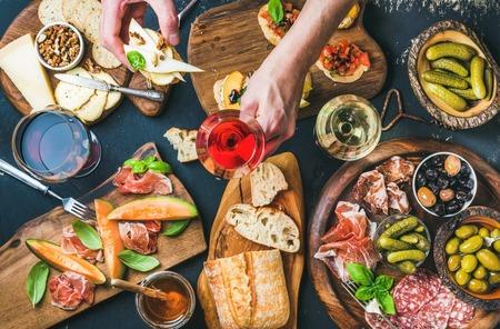 Brushettas, kaas variëteit, mediterrane olijven, augurken, Prosciutto di Parma met meloen, salami, wijn in glazen op zwarte achtergrond, iemands handen met glas rose en brushetta, bovenaanzicht