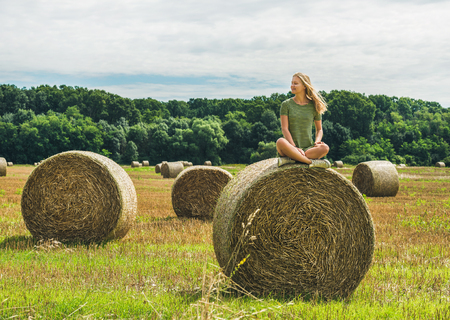 haymow: Young blond girl with long hair sitting legs crossed on haystack and smiling with closed eyes on sunny summer day, Badasconytomaj, Hungary Stock Photo