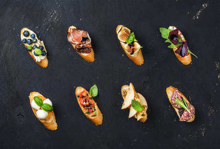 Italian crostini with various toppings on black plywood background, top view Imagens - 61313577