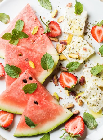 pistachio: Summer watermelon, strawberry and feta cheese salad with wint leaves and pistachios on white plate, top view