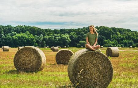 haymow: Young blond lady sitting legs crossed on haystack and smiling on sunny summer day, Badasconytomaj, Hungary Stock Photo
