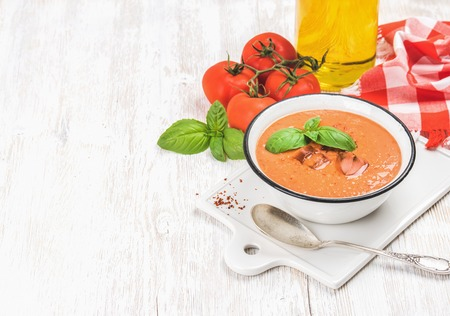 Cold gazpacho soup in bowl with ice, hot pepper and basil served with fresh tomotoes on ceramic board over white wooden background, selective focus, copy space, horizontal composition