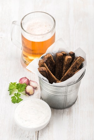 pilsener: Beer snack set. Pint of pilsener in mug and rye bread croutons with garlic cream cheese sauce and fresh parsley over white painted old wooden background, top view, selective focus