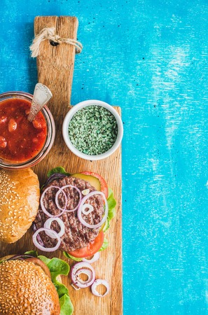 onion rings: Homemade beef burgers with onion, fresh vegetables and tomato sauce on serving wooden board over blue painted background. Top view, copy space, vertical composition