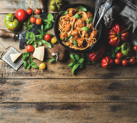 Italian pasta spaghetti with tomato sauce and meatballs in cast iron pan served with Parmesan cheese, fresh basil and colorful tomatoes over old rustic wooden background. Top view, copy space Stock Photo